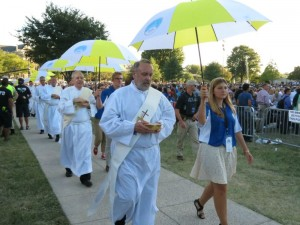 Deacons, accompanied by student volunteers, process to Mass in order to distribute communion.
