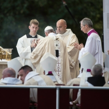 Pope Francis assisted by a deacon and servers
