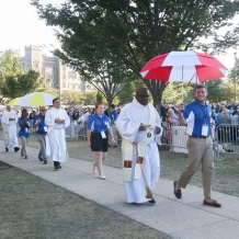 Deacons distributing Communion were escorted by volunteers carrying umbrellas.