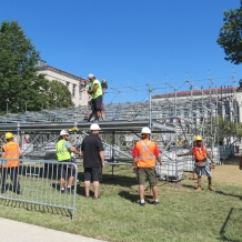 A team of workers places platform pieces on the media riser structure.