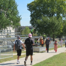 Students walk through fencing on the University Mall past the media riser under construction.