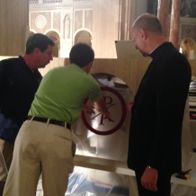 CUA student Matthew Hoffman, carpenter Deacon David Cahoon, and Basilica Rector Monsignor Walter Rossi discuss placement of a mosaic on the altar.