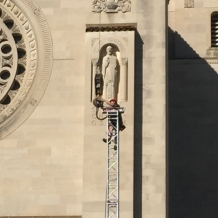 A member of the construction crew works on the top of a support for the roof over the papal altar.
