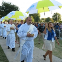 Deacons, accompanied by student volunteers, process to distribute communion.